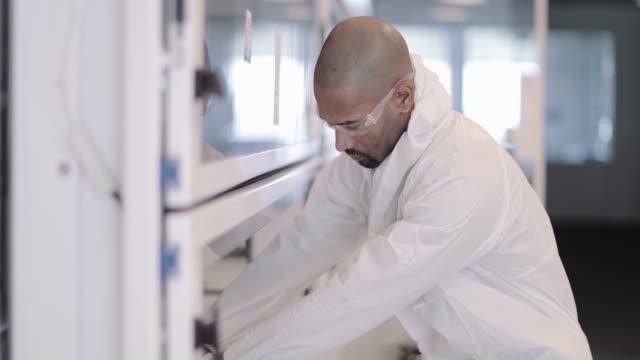 african american scientist looking at sample in a lab - バイオハザードマーク点の映像素材/bロール