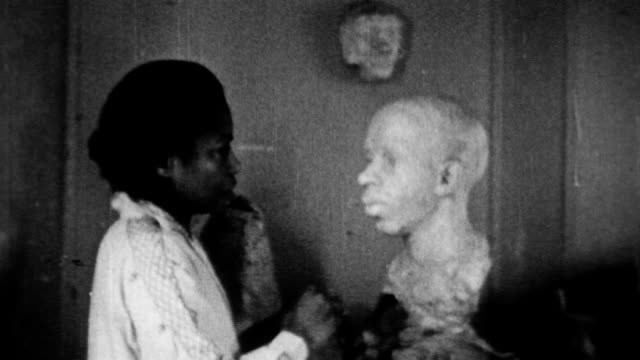 African American sculptor Augusta Savage finishing a statue of a woman / unwraps a large unfinished sculpture / man's face is superimposed on the...