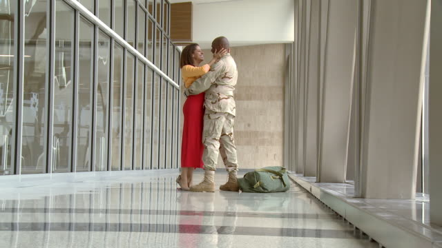 African American soldier greeting girlfriend in airport