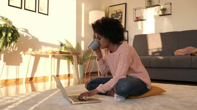 african american student homeschooling, using laptop for online classes and drinking coffee - hot desking stock videos & royalty-free footage