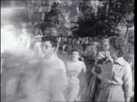 vídeos de stock e filmes b-roll de / african american teenage girl elizabeth eckford is heckled and followed by an angry crowd as she attempts to enter little rock central high school. - seguir atividade móvel