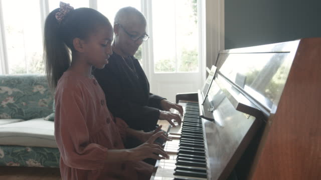 african american teenager plays piano with grandmother, close up - kurzes haar stock-videos und b-roll-filmmaterial