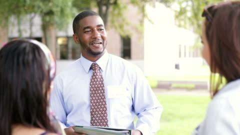 vidéos et rushes de guide d'afro-américains collège étudiants sur le campus - montrer la voie