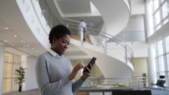 African American using smartphone in modern office