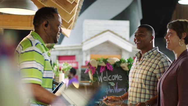 vídeos y material grabado en eventos de stock de slomo. african american winery employee greets a happy interracial couple as they walk to the customer service counter of the gift shop. - técnico telefónico