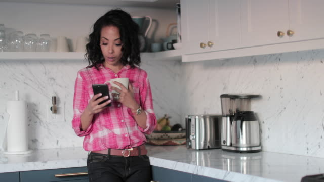 African American woman at home looking at smartphone