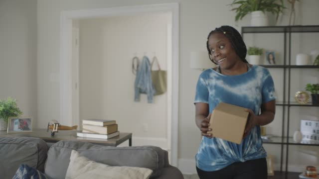 african american woman carries package in to give to her son. - delivering stock videos & royalty-free footage