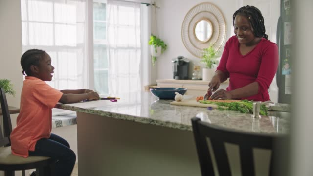 african american woman chops carrots on cutting board while son sits at kitchen counter and watches. - 食材点の映像素材/bロール