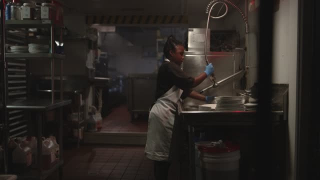 african american woman dances and sings while washing dishes in a restaurant kitchen. - abwaschen stock-videos und b-roll-filmmaterial