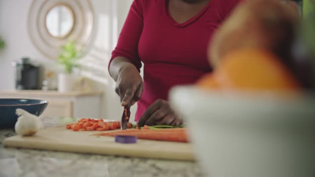 stockvideo's en b-roll-footage met african american woman dices carrots on cutting board and scoops them into mixing bowl on kitchen counter. - plank meubels