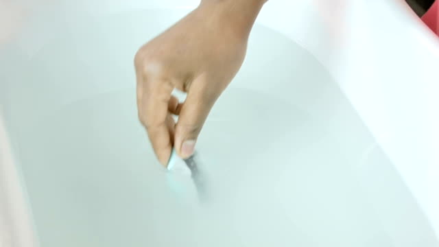 vídeos de stock, filmes e b-roll de hd: afro-americana mulher segurando um bebê testes água do banho - termômetro
