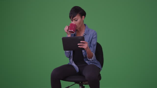 vídeos de stock e filmes b-roll de african american woman in an office chair reading on her tablet on green screen - cadeira
