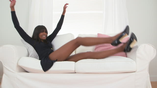 african american woman in black dress falling back on couch - black dress stock videos & royalty-free footage