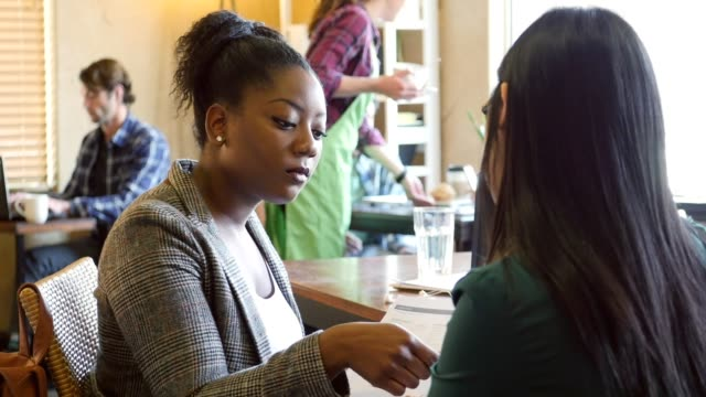 African American woman interviews young woman at a cafe