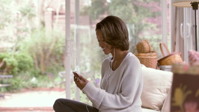vídeos de stock, filmes e b-roll de african american woman listening to earbuds on sofa - cabelo de comprimento médio