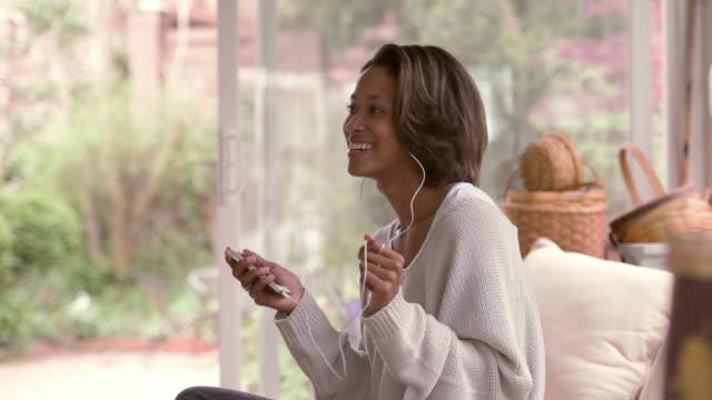 african american woman listening to earbuds on sofa - nodding head to music stock videos & royalty-free footage