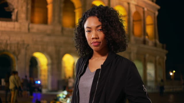 African American woman on vacation standing outside Colosseum in Rome at night