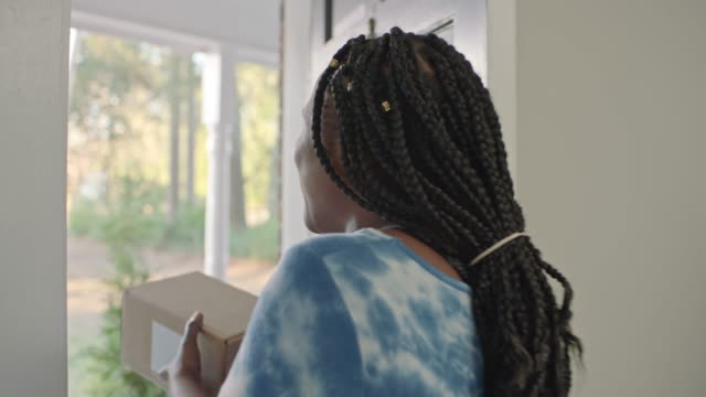 african american woman opens door and receives package delivery with excitement. - united states postal service stock videos & royalty-free footage