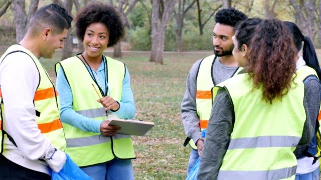vídeos de stock e filmes b-roll de african american woman organizes team of volunteers to cleanup park - social worker
