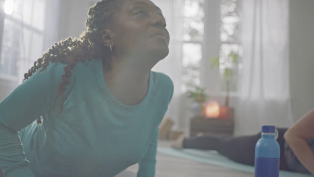 slo mo. african american woman practicing yoga with friend lifts her head up into the sunlight in cobra pose. - motivation stock videos & royalty-free footage