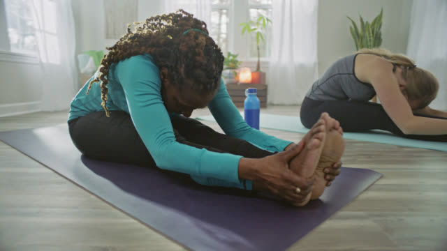 slo mo. african american woman reaches forward to grab her feet in seated forward bend pose in home yoga studio. - yoga stock videos & royalty-free footage