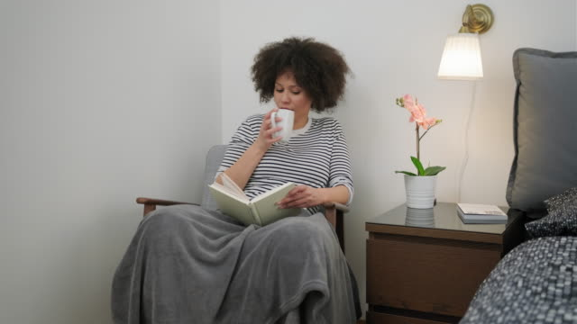 vidéos et rushes de femme d'afro-américain lisant un livre dans la chambre à coucher - coiffure afro