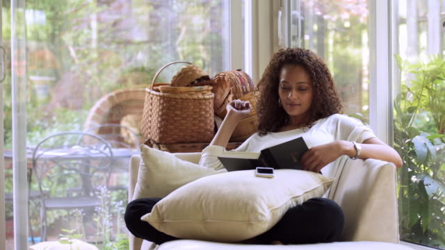 african american woman reading book near window - cushion stock videos and b-roll footage