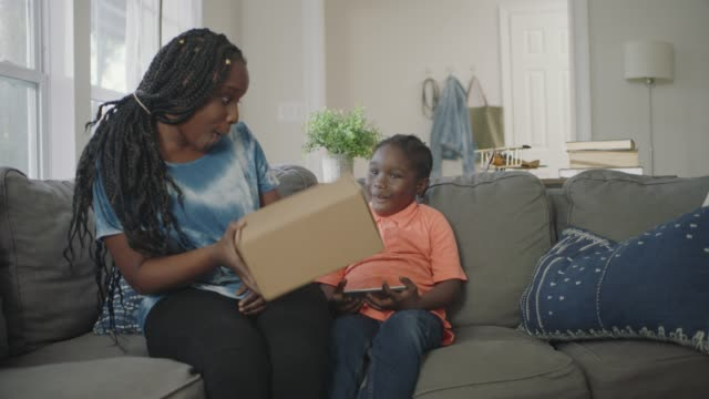 african american woman receives package delivery and shakes box in front of son playing smartphone games on the couch. - postangestellter stock-videos und b-roll-filmmaterial