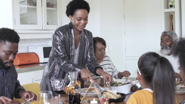 african american woman serves christmas dinner, medium shot - cheerful stock videos & royalty-free footage