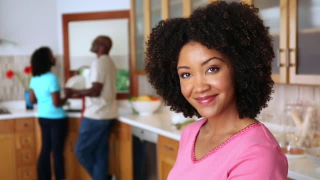 vídeos y material grabado en eventos de stock de african american woman smiling in domestic kitchen - rosa brillante