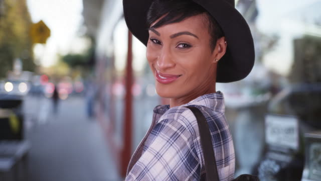 african american woman smiling on busy city street - hat stock videos and b-roll footage