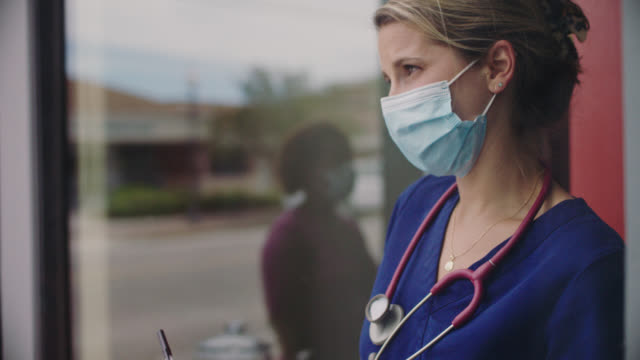 cu african american woman standing outside medical clinic puts on face mask, uses hand sanitizer, knocks on door, speaks briefly with nurse who opens door and records her temperature before going inside - clinic stock videos & royalty-free footage