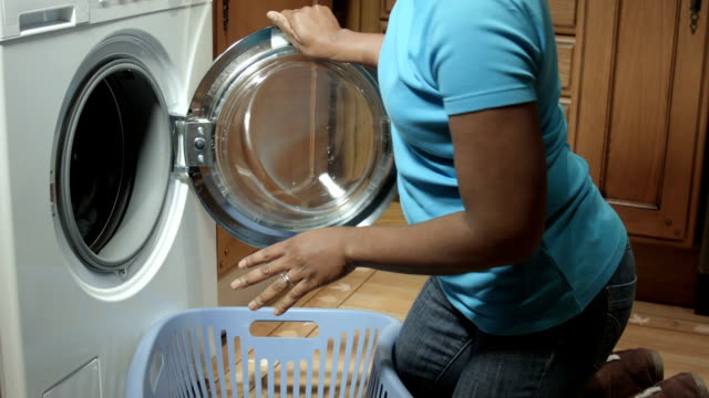 hd: african american woman starting a laundry load - laundry detergent stock videos and b-roll footage