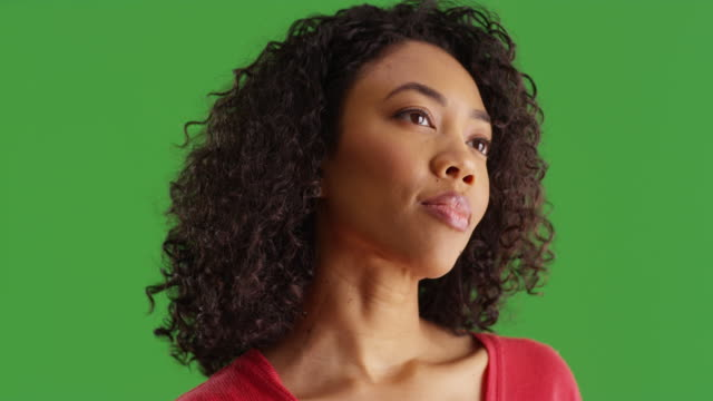 african american woman thinking with small smile on her face on greenscreen - {{asset.href}} stock videos & royalty-free footage