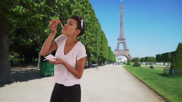 african american woman traveling in paris eats cheesy slice of pizza for lunch - unhealthy eating点の映像素材/bロール