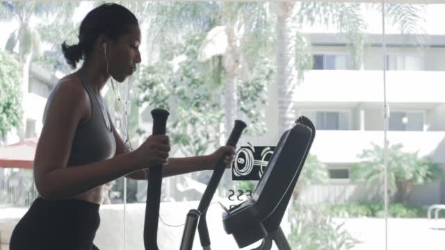 african american woman using elliptical machine - cross trainer stock videos & royalty-free footage