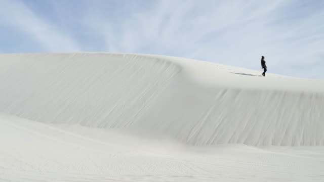african american woman walks on desert dunes, wide - wide stock-videos und b-roll-filmmaterial