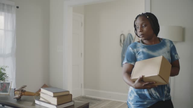 african american woman walks to the door to receive package and carries box in to her son. - delivering stock videos & royalty-free footage