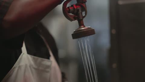vídeos y material grabado en eventos de stock de cu slo mo. african american woman washes dishes in a restaurant kitchen. - clean