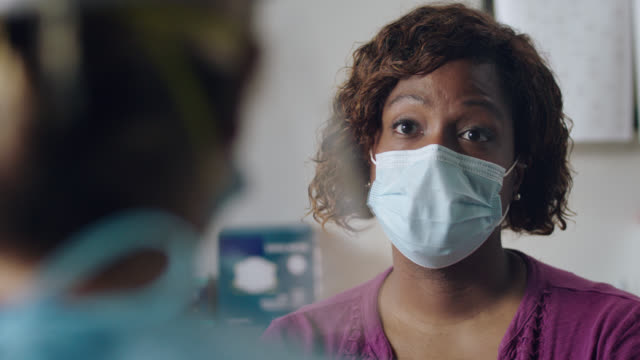 cu african american woman wearing protective face mask gets tested for covid-19 in medical facility - responsibility stock videos & royalty-free footage