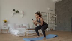 African american woman with phone squats at home