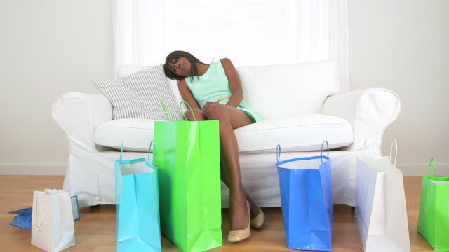 vídeos de stock, filmes e b-roll de african american woman with shopping bags resting on couch - cansado