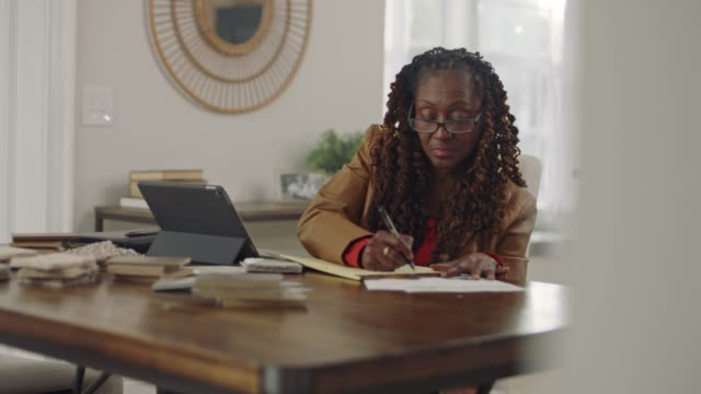 african american woman working from home puts on glasses and studies paperwork in home office. - using laptop stock videos & royalty-free footage