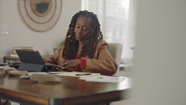 African American woman working from home with tablet computer shuffles papers around on desk.