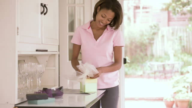 african american woman wrapping gift - mid length hair stock videos & royalty-free footage