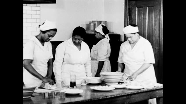stockvideo's en b-roll-footage met african american women learn household skills at wpa training classes / women making food in large kitchen / learning to make beds / health care... - huishuidkunde