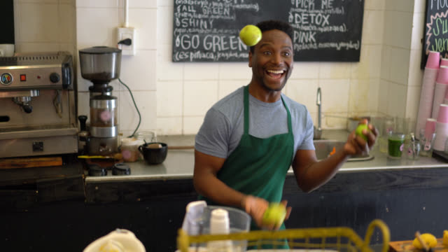 african american worker at a juice bar juggling with fruits having fun - juggler stock videos and b-roll footage