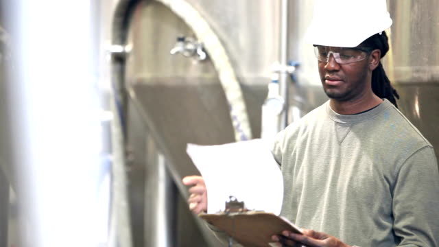 African American worker in factory looking at clipboard