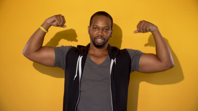 african american young man showing off his muscles - bicep stock videos and b-roll footage
