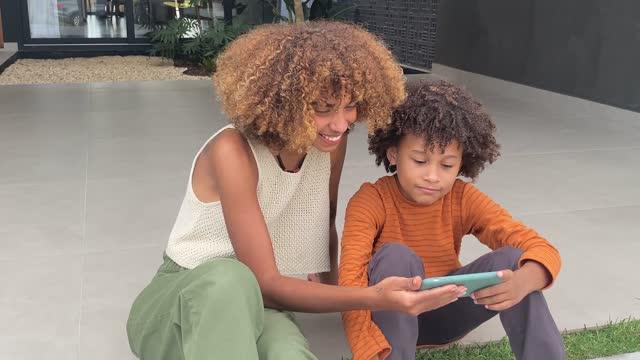 vídeos de stock, filmes e b-roll de afro-americana jovem e seu irmão mais novo jogando jogo em telefone inteligente - smart